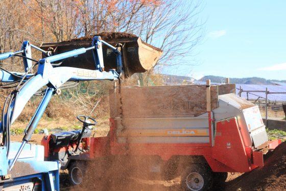 堆肥を散布車に積み込み中